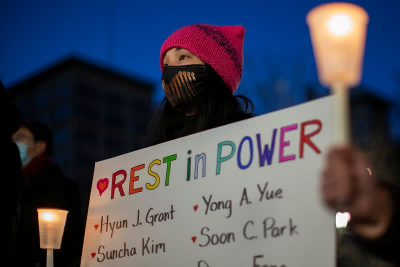 A woman holds a sign during a peace vigil to mourn the victims of anti-Asian hate crimes in New York
