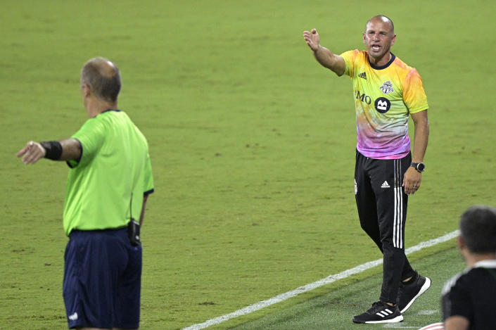 Toronto FC head coach Chris Armas, right, argues with an official during the second half of an MLS soccer match against FC Cincinnati, Saturday, June 26, 2021, in Orlando, Fla. (AP Photo/Phelan M. Ebenhack)