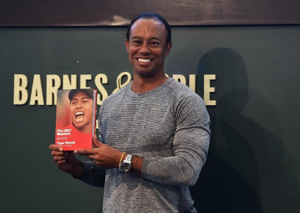 "The 14-time major champ golfer Tiger Woods holds a copy of his new book ""The 1997 Masters: My Story"" at a book signing in New York (AFP Photo/TIMOTHY A. CLARY)"