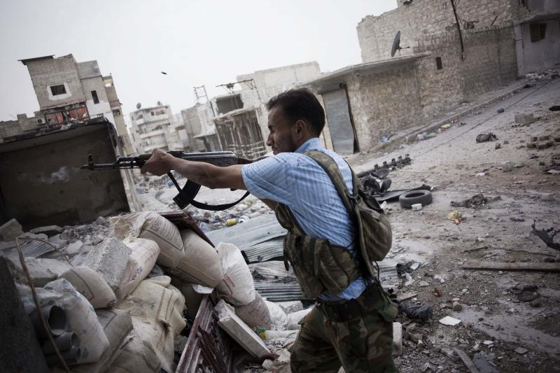 In this Saturday, Oct. 20, 2012 photo, a Free Syrian Army fighter shoots his machine gun towards Syrian Army positions in the Amriya district of Aleppo, Syria. (AP Photo/ Manu Brabo)