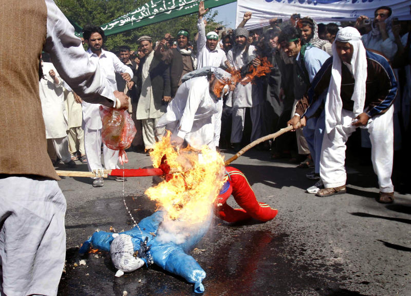 Afghan protestors burn an effigy of U.S. President Barack Obama during a demonstration in Jalalabad, Afghanistan on Sunday, April 3, 2011. Afghan protests against the burning of a Quran in Florida entered a third day with a demonstration in the major eastern city Sunday, while the Taliban called on people to rise up, blaming government forces for any violence. (AP Photo/Rahmat Gul)