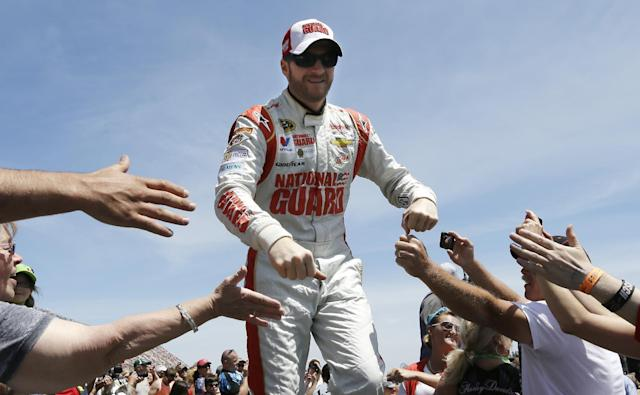 Dale Earnhardt Jr. greets fans during driver introductions before the NASCAR Quicken Loans 400 auto race at Michigan International Speedway in Brooklyn, Mich., Sunday, June 15, 2014. (AP Photo/Carlos Osorio)