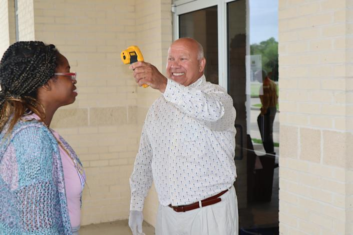 "A volunteer at Life Tabernacle Church outside Baton Rouge, La., checks a woman's temperature before she can enter Sunday's service. <span class=""copyright"">(Woody Jenkins / Central City News)</span>"