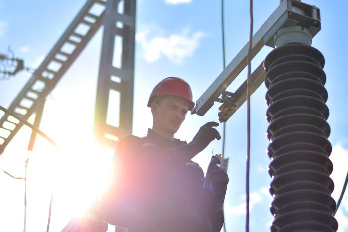 A worker with power equipment in the background