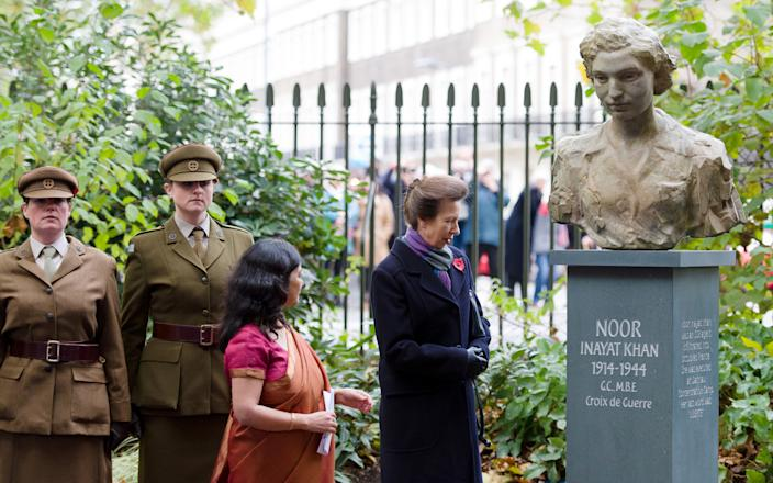 Britain's Princess Anne looks at a statue of Noor Inayat Khan after unveiling it in a ceremony in Gordon Square Gardens, central London on November 8, 2012 in London, England. Noor Inayat Khan worked as a radio operator for the Women's Auxiliary Air Force before being recruited by the Special Operations Executive as an agent, working behind enemy lines in Paris, France.  She was eventually captured, tortured and beaten before being executed at Dachau Concentration Camp, aged 30. AFP PHOTO / LEON NEAL        (Photo credit should read LEON NEAL/AFP via Getty Images)