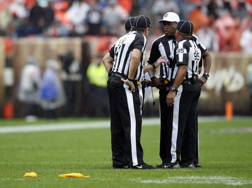 FILE - In this Sunday, Sept. 9, 2018, file photo, referee Shawn Smith, second from right, and members of his crew meet for a conference during an NFL football game between the Pittsburgh Steelers and the Cleveland Browns in Cleveland. NFL officials come from a pipeline established by the NleagueL that seeks to identify people with the right skill set, temperament and judgment to handle a thankless job week after week. (Jeff Haynes/AP Images for Panini, File)