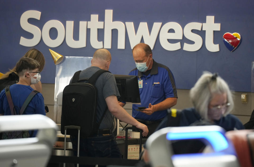 FILE - In this Wednesday, June 16, 2021, file photo, a Southwest Airlines ticketing agent helps a traveller at the check-in counter at Denver International Airport in Denver. This summer is already shaping up to be a difficult one for air travelers. Southwest Airlines customers have struggled with thousands of delays and hundreds of canceled flights this month because of computer problems, staffing shortages and bad weather. (AP Photo/David Zalubowski, File)
