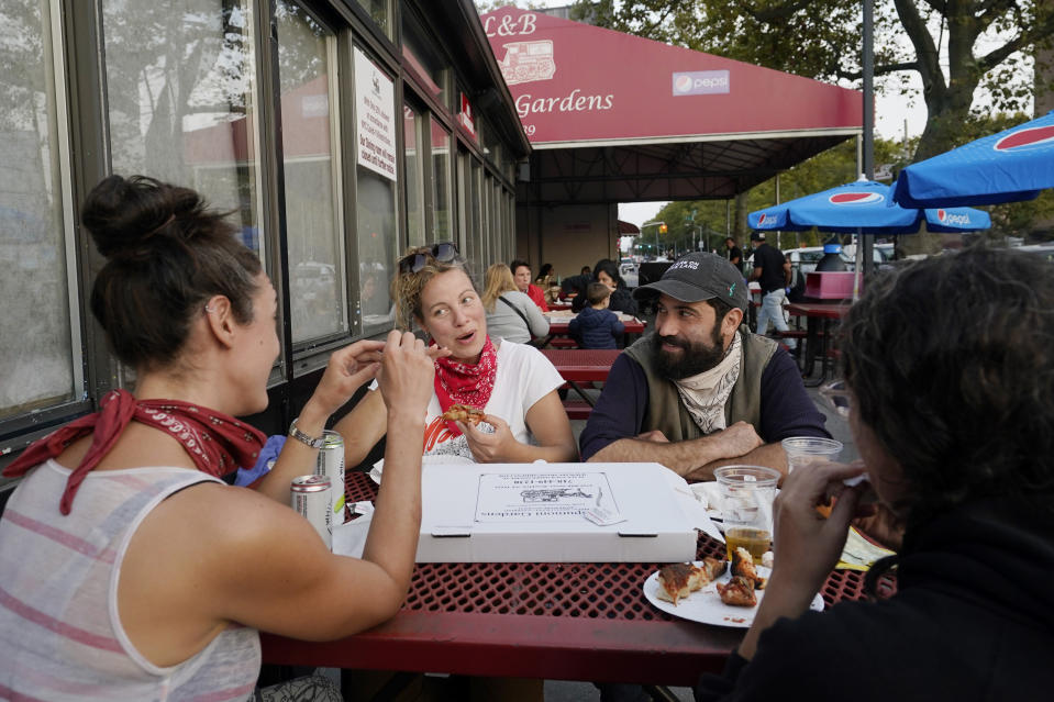 Nora Feher, Sarah Howard, Mike Sternfeld and Annie Simon, from left, share a pizza while eating outdoors, Sunday, Oct. 4, 2020, at L&B Spumoni Gardens in the Brooklyn borough of New York. Feher and Sternfeld both work in the food service industry. The restaurant is in a Zip Code that has seen a spike in coronavirus cases recently. On Sunday, New York's mayor said he asked the state for permission to close schools and reinstate restrictions on nonessential businesses in several neighborhoods because of a resurgence of virus cases. Should restrictions be imposed, the restaurant may have to close its outdoor dining area and restrict itself to takeout and delivery only. (AP Photo/Kathy Willens)
