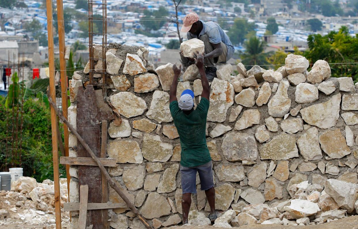Haitians construct a wall as they rebuild a destroyed house on Jan. 7, 2011.