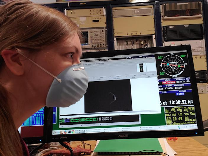 """A researcher at Arecibo Observatory comparing her mask to the """"mask"""" the 1998 OR2 asteroid has on."""