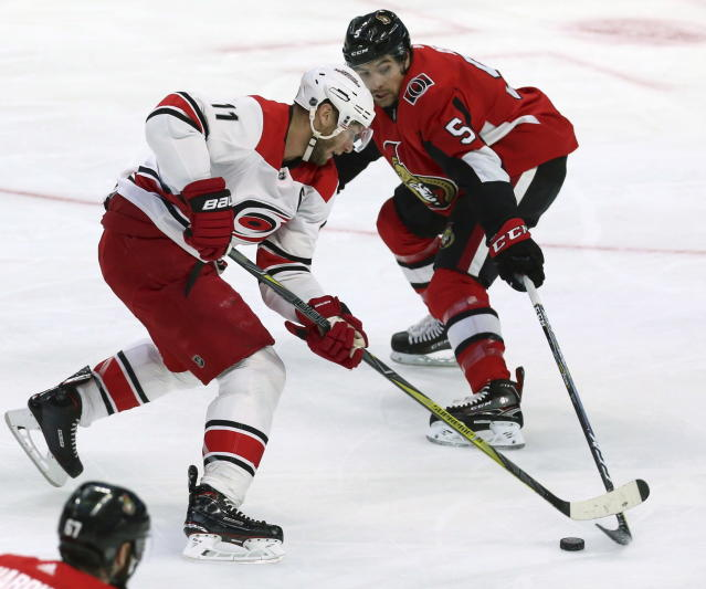 Ottawa Senators' Cody Ceci (5) attempts to poke-check Carolina Hurricanes' Jordan Staal (11) during first-period NHL hockey game action in Ottawa, Ontario, Saturday, March 24, 2018. (Fred Chartrand/The Canadian Press via AP)