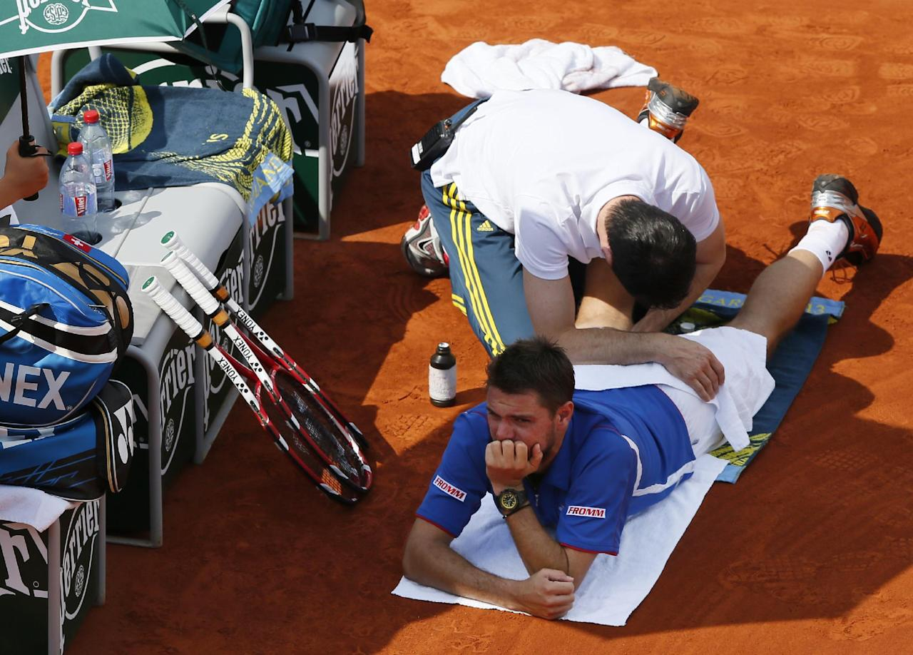 (FILES) This file photo taken on June 03, 2013 shows Switzerland's Stanislas Wawrinka being treated by a medic during a French tennis Open round of 16 match against France's Richard Gasquet at the Roland Garros stadium in Paris.World number four Stan Wawrinka withdrew from the Rio Olympics with a back injury on August 02, 2016, dealing another body blow to the tennis tournament which has been hit by a series of high-profile pull-outs. The 31-year-old is the third Swiss player to withdraw after Roger Federer and Belinda Bencic who also scratched from the event through injury. (AFP Photo/PATRICK KOVARIK)