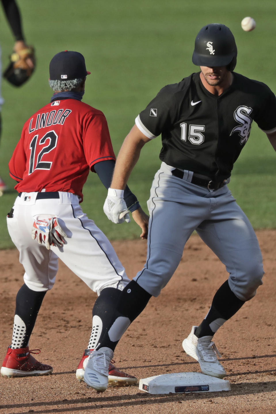 Chicago White Sox's Adam Engel (15) is safe at second base on a double as Cleveland Indians' Francisco Lindor (12) waits for the ball in the sixth inning in a baseball game, Wednesday, July 29, 2020, in Cleveland. (AP Photo/Tony Dejak)