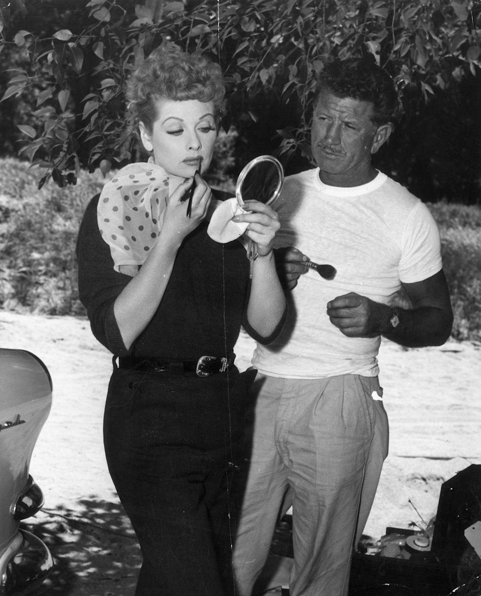 """<p>Lucille fixes her lipstick as her makeup artist stands by. The Hollywood beauty was known for her famous red hair, but few know it's not her natural hair color. When she was a 27-year-old aspiring actress, she <a href=""""https://www.popsugar.co.uk/beauty/Lucille-Ball-Natural-Hair-Colour-46472035"""" rel=""""nofollow noopener"""" target=""""_blank"""" data-ylk=""""slk:dyed it red"""" class=""""link rapid-noclick-resp"""">dyed it red</a> to separate herself from her competition.</p>"""