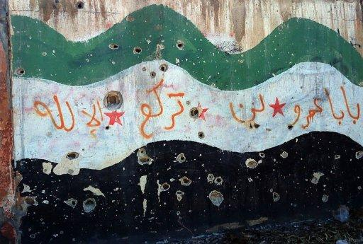A handout picture released by the Syrian opposition's Shaam News Network shows a bullet-riddled wall depicting a pre-Baath era national flag in the Inshaat neighborhood of Homs