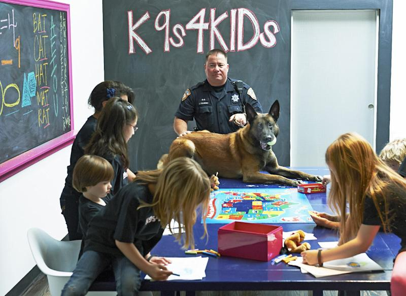 In this Feb. 18, 2013 photo provided by K9s4KIDS, Harris County Sheriff's Deputy John Palermo and his dog Rico meet with children at the TutorVille HUB in Houston. Schools have beefed up security, staged mock drills and added metal detectors, cameras and alarms to prevent violence. Some think teachers should be armed and the National Rifle Association wants armed police in every American school. Kristi Schiller thinks some special dogs might do the trick. She wants her charity, K9s4KIDS, to do for schools what it's done for police departments in the U.S. - place scores of trained dogs among their ranks through the nonprofit set up in 2009. (AP Photo/K9s4KIDS, Josh Welch)
