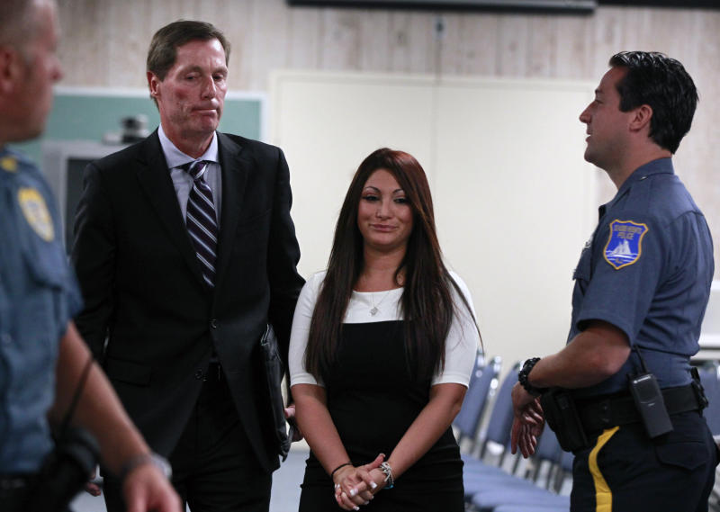 """""""Jersey Shore"""" cast member Deena Cortese, center, walks with her attorney Michael Pappa, left, in court after a hearing Tuesday, July, 3, 2012, in Seaside Heights, N.J. The """"Jersey Shore"""" cast member was in Seaside Heights municipal court on a change of interfering with traffic for an incident in which police say she was dancing in a street and blocking the flow of traffic. Cortese pleaded guilty to failing to use the sidewalk and paid a $106 fine.(AP Photo/Mel Evans)"""
