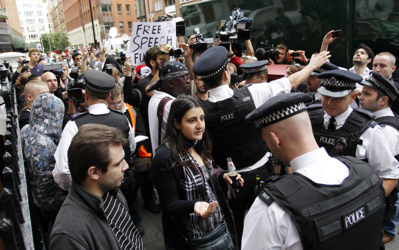 British police officers move the protesters in support of WikiLeaks founder Julian Assange from the front of the Ecuadorian Embassy in central London, London, Thursday, Aug. 16, 2012. WikiLeaks founder Julian Assange entered the embassy in June in an attempt to gain political asylum to prevent him from being extradited to Sweden, where he faces allegations of sex crimes, which he denies. (AP Photo/Sang Tan)
