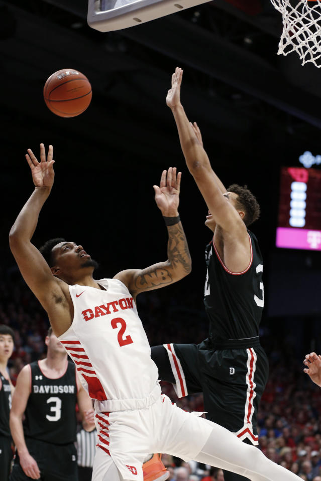 Dayton guard Ibi Watson (2) shoots over Davidson forward Nelson Boachie-Yiadom, right, during the first half of an NCAA college basketball game Friday, Feb. 28, 2020, in Dayton, Ohio. (AP Photo/Gary Landers)