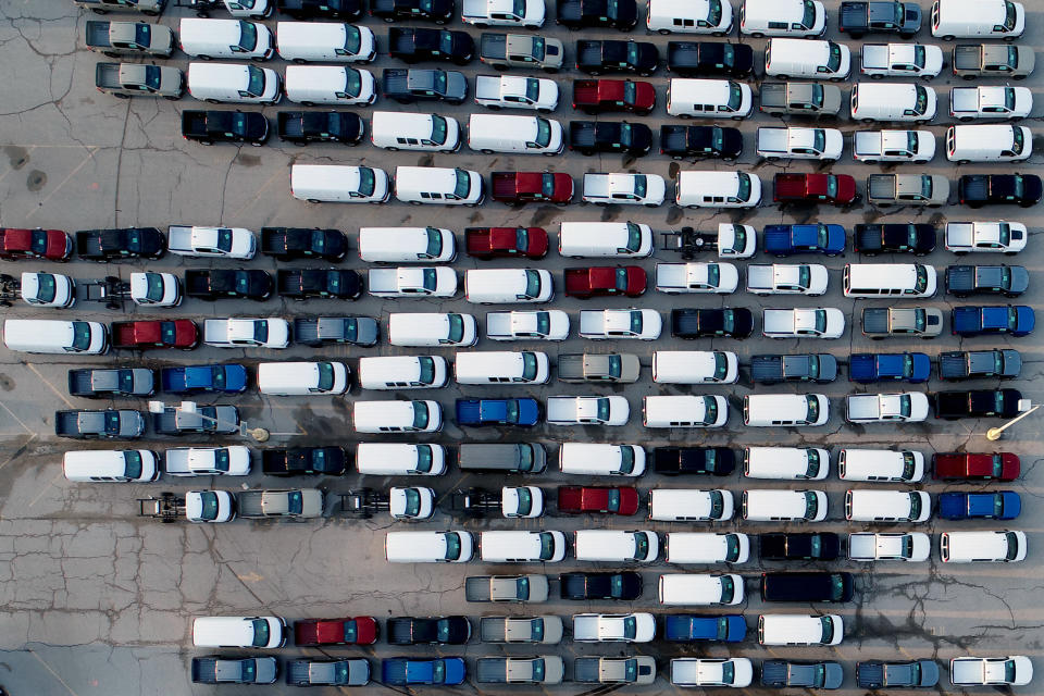 In this aerial photo, mid-sized pickup trucks and full-size vans are seen in a parking lot outside a General Motors assembly plant where they are produced Wednesday, March 24, 2021, in Wentzville, Mo. As the U.S. economy awakens from its pandemic-induced slumber, a vital cog is in short supply: the computer chips that power our cars and other vehicles, and a vast number of other items we take for granted. Ford, GM and Stellantis have started building vehicles without some computers, putting them in storage with plans to retrofit them later. (AP Photo/Jeff Roberson)