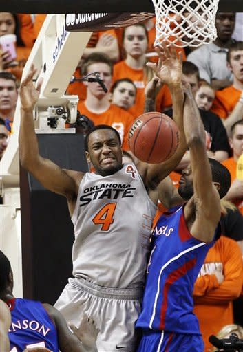 Oklahoma State guard Brian Williams (4) is fouled by Kansas forward Justin Wesley, right, as he goes up for a shot in the first half of an NCAA college basketball game in Stillwater, Okla., Monday, Feb. 27, 2012. (AP Photo/Sue Ogrocki)