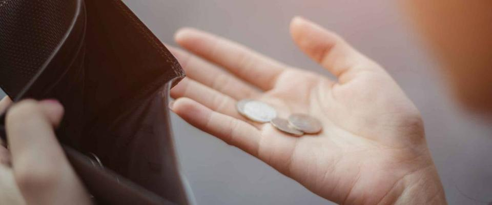 Person holding change from an empty wallet
