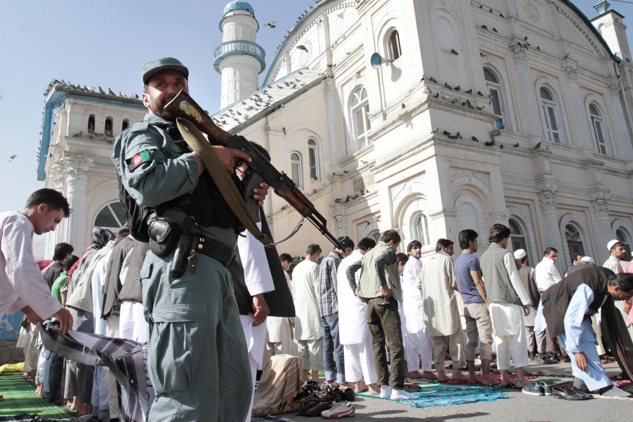 An Afghan policeman stands guard outside Shah-e- Dushamshera's mosque where Afghans offer the Eid al-Fitr's prayers that marks the end of holy fasting month of Ramadan in Kabul, Afghanistan, Sunday, Aug. 19, 2012. (AP Photo/Musadeq Sadeq)