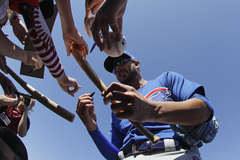 Chicago Cubs' Kris Bryant gives autographs to fans before a spring training baseball game against the Seattle Mariners, Monday, Feb. 24, 2020, in Peoria, Ariz. (AP Photo/Darron Cummings)