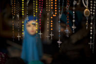 FILE - In this March 4, 2017 file photo, rosary beads are displayed for selling next to a mannequin wearing a headscarf in a market stall at The Hague, The Netherlands. Europe has witnessed many more jihadist attacks on its soil than the United States since 9/11, and analysts say a variety of reasons account for that. They point to Europe's homegrown extremists, weaknesses in counterterrorism strategies and geography. They note that many Muslims in Europe are disadvantaged and and some harbor grievances against the countries where they live. Western Europe has struggled to integrate significant Muslim populations into mainstream society. (AP Photo/Emilio Morenatti, File)