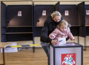 A woman wearing a face mask to protect against the coronavirus, with a child, casts her ballot at a polling station during the second round of a parliamentary election in Vilnius, Lithuania, Sunday, Oct. 25, 2020. Polls opened Sunday for the run-off of national election in Lithuania, where the vote is expected to bring about a change of government following the first round, held on Oct. 11, which gave the three opposition, center-right parties a combined lead. (AP Photo/Mindaugas Kulbis)