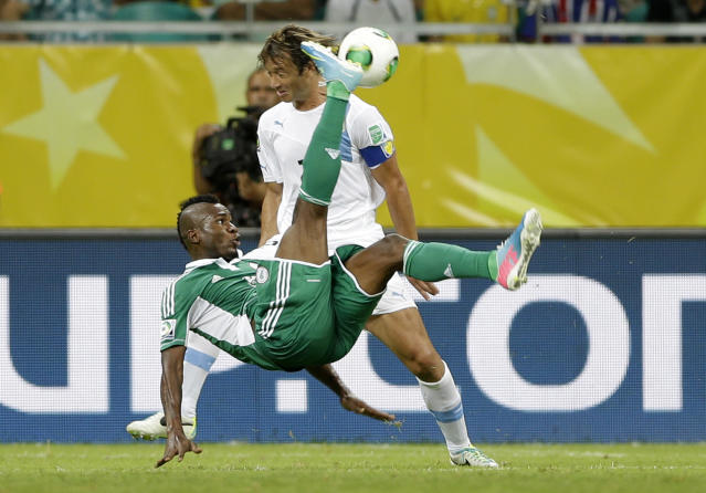 FILE - In this June 20, 2013, file photo, Nigeria's Brown Ideye, front, makes a bicycle kick in front if Uruguay's Diego Lugano during the soccer Confederations Cup group B match between Nigeria and Uruguay at Fonte Nova stadium in Salvador, Brazil. After impressing on their way to the second round in each of their first two FIFA World Cup appearances, 1994 and 1998, Nigeria have struggled since: going out at the group stage three times while taking just two points from their last eight matches in the finals. (AP Photo/Natacha Pisarenko, File)