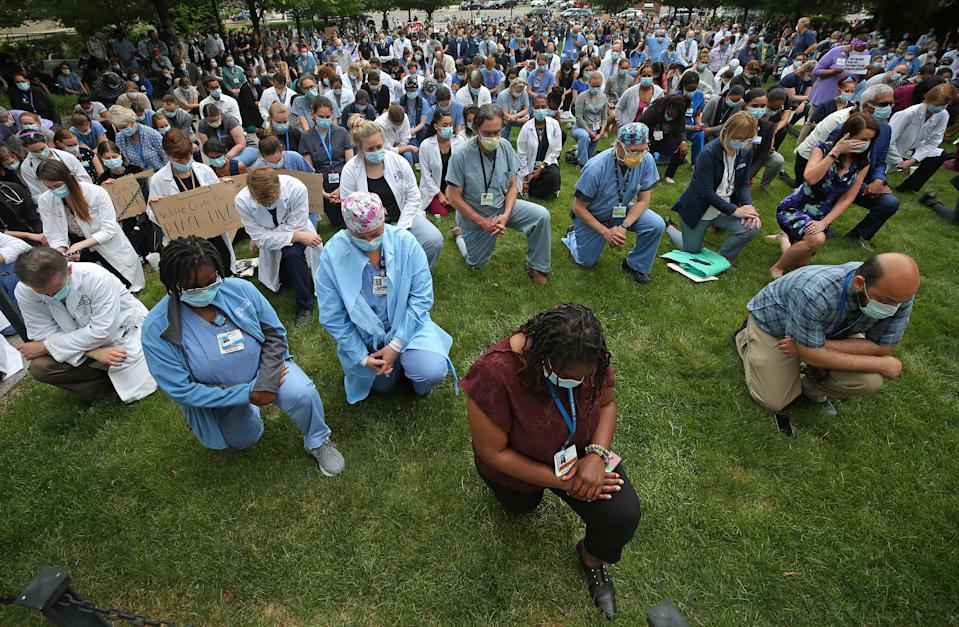 Doctors and nurses at Brigham and Women's Hospital in Boston kneel during a vigil in memory of George Floyd and reflection on racial injustice. (Photo by David L. Ryan/The Boston Globe via Getty Images)