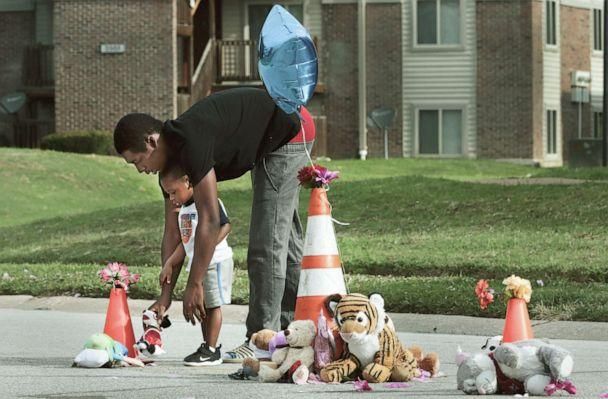 PHOTO: Canfield Green Apartments resident Marcus Hill helps his son Messiah Hill, 2, place a stuffed animal at a newly rebuilt memorial to Michael Brown, Jr. on Thursday, Aug. 8, 2019, in Ferguson, Mo. (Robert Cohen/AP)