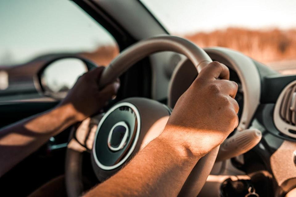 A person holding a car steering wheel