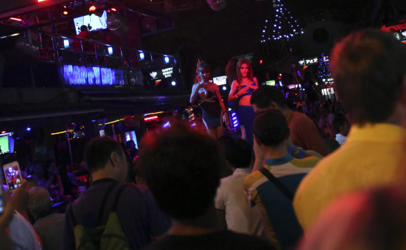 In this March 12, 2014 photo, foreign tourists watch a performance by nightclub dancers in Phuket province, southern Thailand. Thailand's sapphire blue waters, wildlife parks, delicious cuisine and raunchy red light districts have attracted tourists for decades. Phuket is one of Thailand's tourism honeypots. Tourists flock here in droves each year for its sun, sand and laid back ambience. And some lose their passports along the way. (AP Photo/Sakchai Lalit)