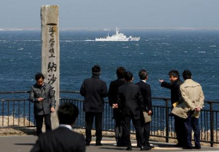 A Japanese Coast Guard vessel PS08 Kariba sails off Cape Nosappu in Nemuro on Japan's Hokkaido island, with part of the islands known as the Northern Territories in Japan and the Southern Kurils in Russia visible the background, April 14, 2017. REUTERS/Issei Kato/Files