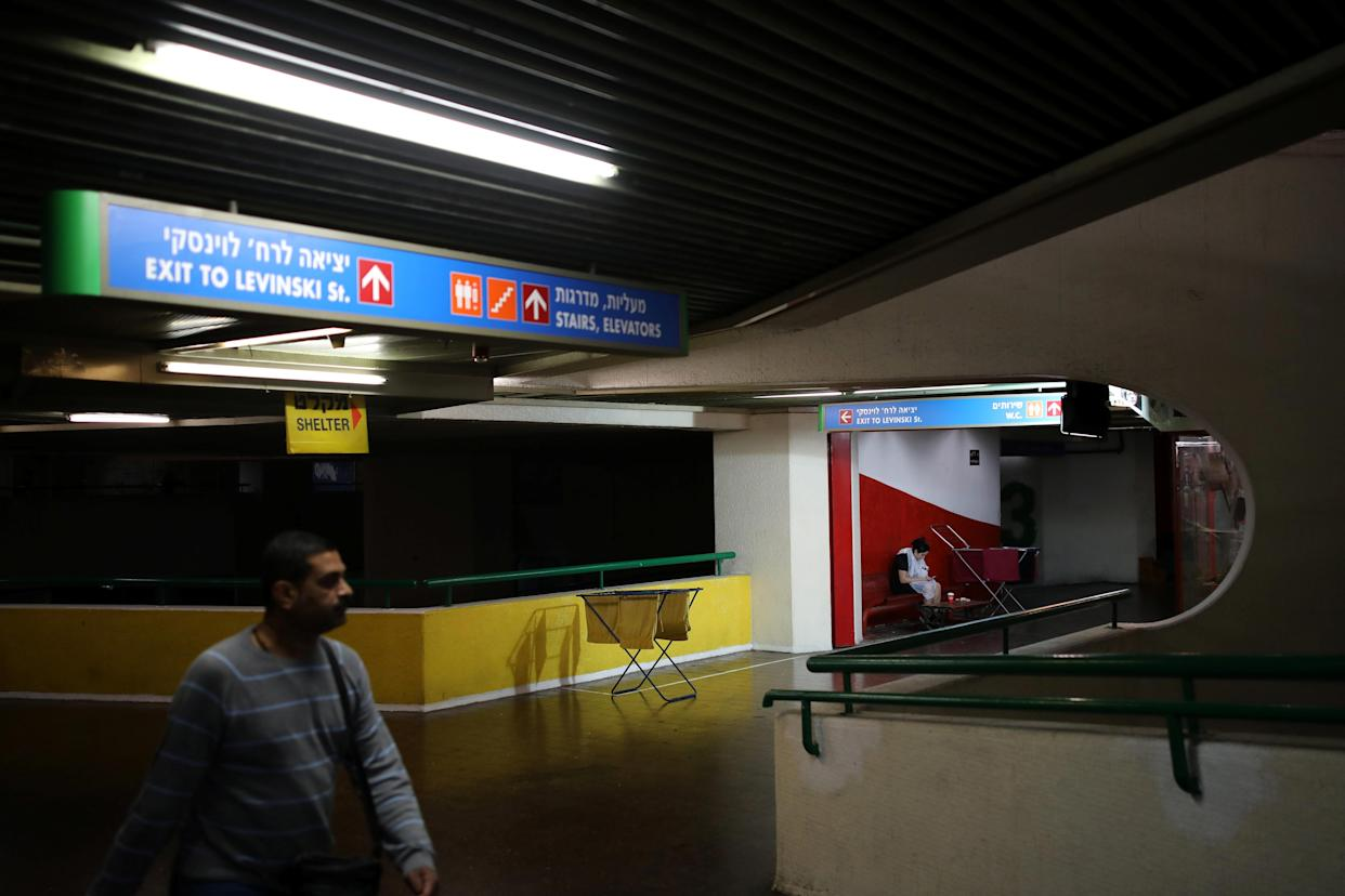 A man walks by as a woman waits outside a hair salon at the Central Bus Station on Jan. 11. (Photo: Corinna Kern/Reuters)