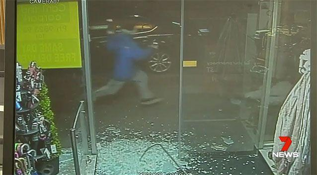 Mr Lee tries to run away but falls as the burglar (in blue) approaches him. Source: 7 News