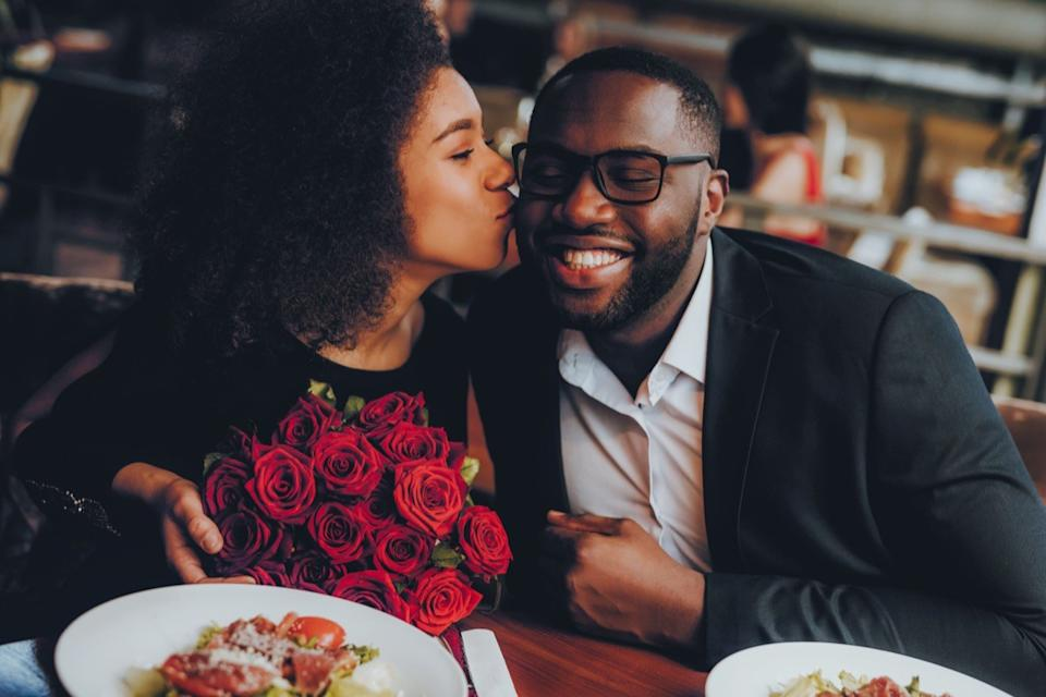 Black couple at restaurant with roses