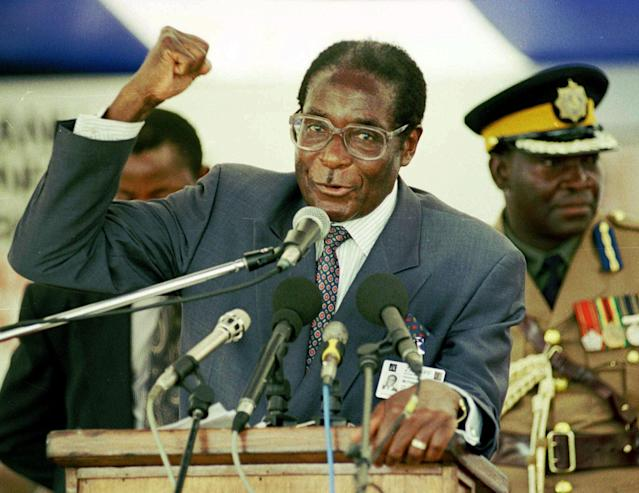 <p>Mugabe gives a speech concerning land resettlement during the Third National People's Conference at Mary Mount Teachers' College in Mutare, Zimbabwe, in 1997. (Photo: C. Collingridge/AP) </p>