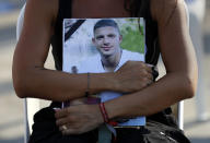 A relative of a victim who was killed in the massive blast last year at the Beirut port holds hugs his portrait as she attends a mass held to commemorate the first year anniversary of the deadly blast, at the Beirut port, Lebanon, Wednesday, Aug. 4, 2021. United in grief and anger, families of the victims and other Lebanese came out into the streets of Beirut on Wednesday to demand accountability as banks, businesses and government offices shuttered to mark one year since the horrific explosion. (AP Photo/Hussein Malla)