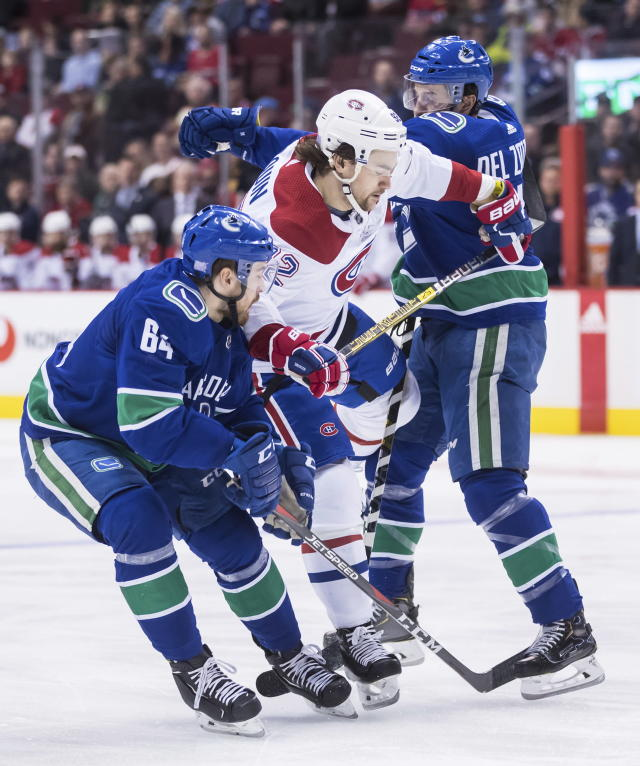 Montreal Canadiens' Jonathan Drouin, center, is checked by Vancouver Canucks' Michael Del Zotto, right, in front of Tyler Motte, left, during the first period of an NHL hockey game in Vancouver, British Columbia, Saturday, Nov. 17, 2018. (Darryl Dyck/The Canadian Press via AP)