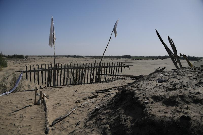 White flags and a pile of burned refuse is all that remains of an old shrine named Imam Asim on the outskirts of Hotan (AFP Photo/GREG BAKER)