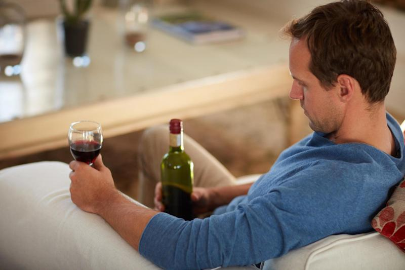 A man drinks a glass of red wine at home in the day time: Getty Images