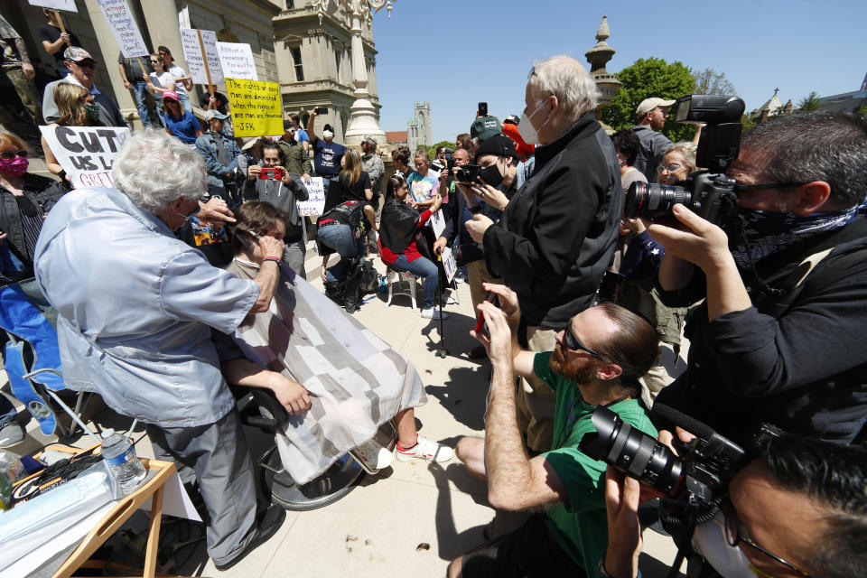 The media record barber Karl Manke, of Owosso, giving a free haircut to Parker Shonts on the steps of the State Capitol during a rally in Lansing, Mich., Wednesday, May 20, 2020. Barbers and hair stylists are protesting the state's stay-at-home orders, a defiant demonstration that reflects how salons have become a symbol for small businesses that are eager to reopen two months after the COVID-19 pandemic began. (AP Photo/Paul Sancya)
