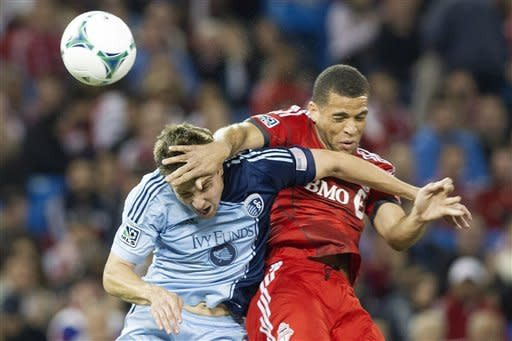 Toronto FC 's Darel Russell, right, battles for the ball with Sporting Kansas City's Matt Besler during second half MLS soccer action in Toronto on Saturday, March 9, 2013. (AP Photo/The Canadian Press, Chris Young)