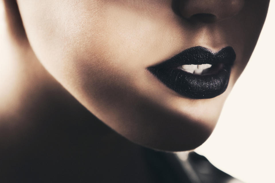 Close-up of beautiful black lips, illuminated with a selective spotlight.