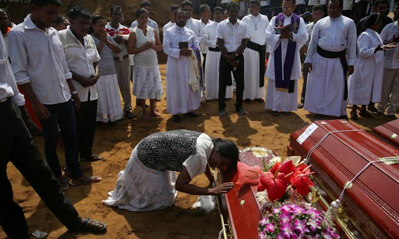 People gather at a mass burial of victims at a cemetery near St Sebastian church in Negombo, Sri Lanka