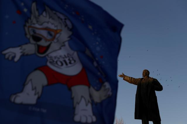 A flag depicting Zabivaka, official mascot of Russia 2018 World Cup, flutters next to a statue of Soviet state founder Vladimir Lenin in Volgograd, Russia, June 21, 2018. As well as shooting all the matches, Reuters photographers are producing pictures showing their own quirky view from the sidelines of the World Cup. REUTERS/Sergio Perez TPX IMAGES OF THE DAY