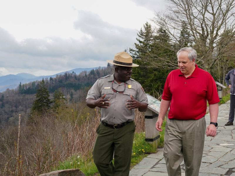 ADDS NAME OF PARK SUPERINTENDENT - This Wednesday, May 6, 2020 image from a tweet by Interior Secretary David Bernhardt, the Interior Secretary talks with Cassius Cash, the park superintendent, as he visits National Parks Service employees at Great Smoky Mountains National Park. While the Interior Secretary asked visitors to social distance when the park reopens on May 9, neither Bernhardt nor park staff wore face masks in the photos, as they talked and walked inches apart during his visit on Tuesday, May 5.  (National Parks Service via AP)
